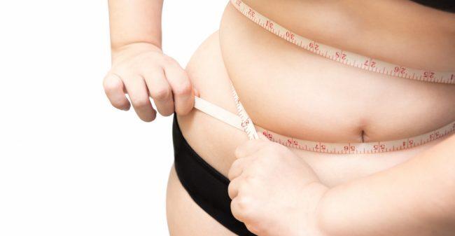 Een lichaam met overgewicht dat samengeknepen wordt door een meetlint